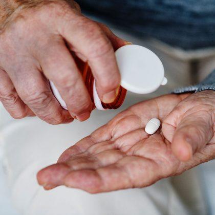 Äldre person som doserar medicin i hand